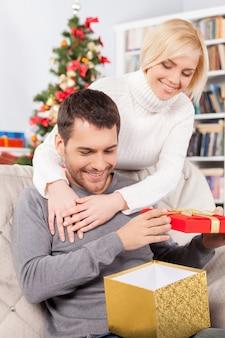정말 좋은 선물입니다! 잘생긴 젊은 남자가 소파에 앉아 선물 상자를 들고 그녀의 여자 친구가 그 뒤에 서서 웃고 있는 동안