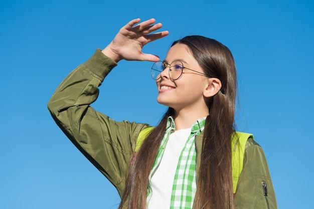 Какой вид. счастливая девушка в очках смотрит вдаль на голубом небе. чувство зрения. уход за зрением и проверка зрения. защита зрения. здоровье глаз ребенка. детская офтальмология. взгляд в будущее.