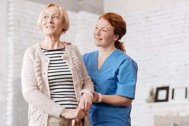 경치 죽이네. 환자를 손으로 잡고 단단히 서있는 환자를 배정하는 달콤한 돌보는 개인 간호사