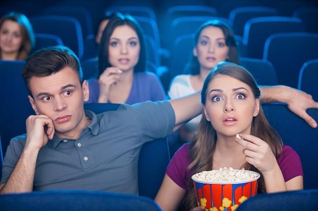 Что я здесь делаю? скучно молодой человек сидит рядом со своей возбужденной женщиной во время просмотра фильма в кинотеатре