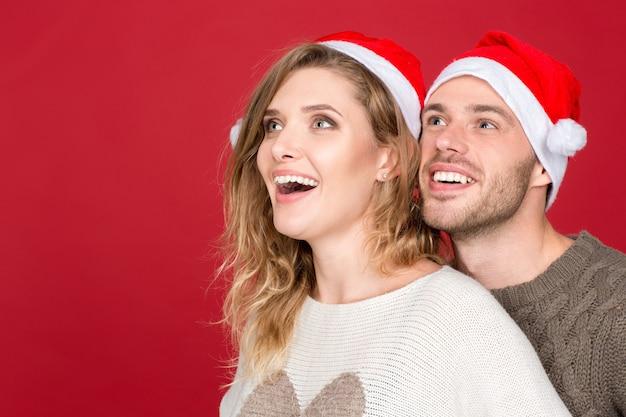 Какое предложение! крупным планом портрет возбужденной молодой пары, счастливо глядя в сторону copyspace сбоку