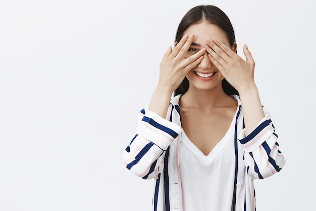 What are you hiding from me. portrait of intrigued playful charming woman in striped blouse, covering eyes with palms and peeking through fingers, smiling broadly, waiting surprise