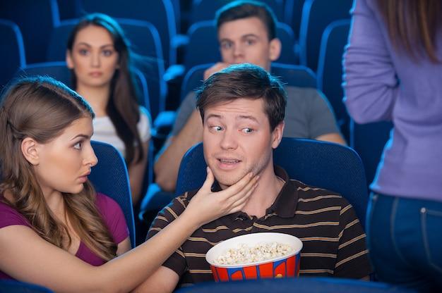 На что ты смотришь? молодой человек смотрит на ягодицы женщины, сидя вместе со своей девушкой в кино