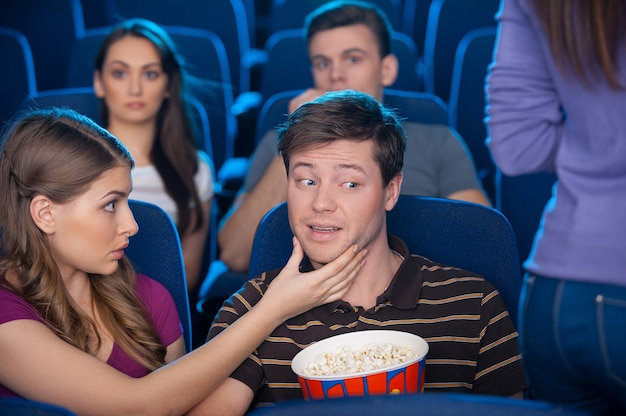 What are you looking at? young man looking at the woman buttocks while sitting together with his girlfriend at the cinema