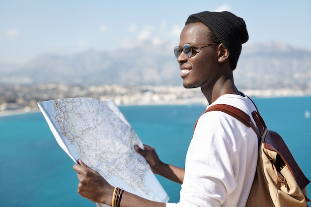 What a beautiful landscape! happy excited afro american backpacker using paper map while standing on viewing point high above blue sea and studying surroundings during his trip. travel and adventure