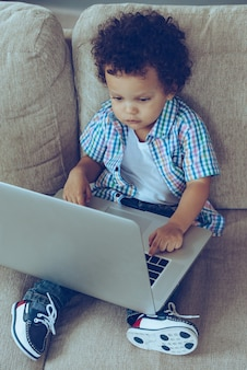What button should i push? high angle view of little african baby boy using his laptop while sitting on the couch at home