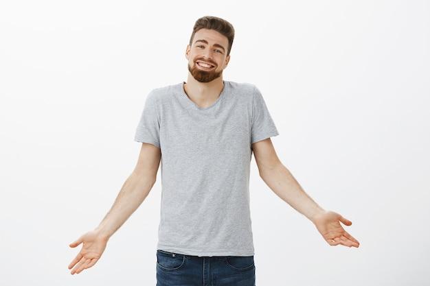 私は完璧な彼氏と言えるでしょうか。腕を広げてひげをすくめてカリスマ的な魅力的なヨーロッパ人、喜ばしいかわいい笑顔と満足のいく仕事の自信を褒める