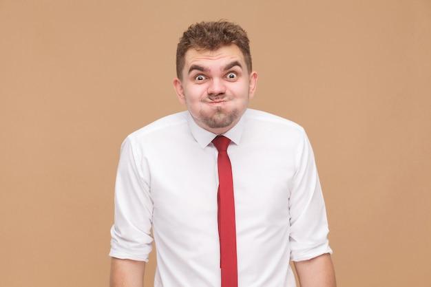 Какие? сумасшедший смешной человек с большим глазом, смотрящим в камеру. концепция деловых людей, хорошие и плохие эмоции и чувства. студийный снимок, изолированные на светло-коричневом фоне