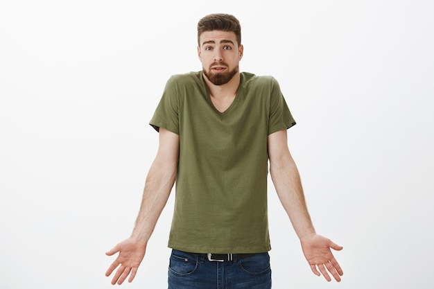 Что я сделал не так. портрет сбитого с толку парня не может понять, что произошло, пожимает плечами и держится за руки боком, поднимая брови, чувствуя разочарование и сомнение, пытаясь извиниться