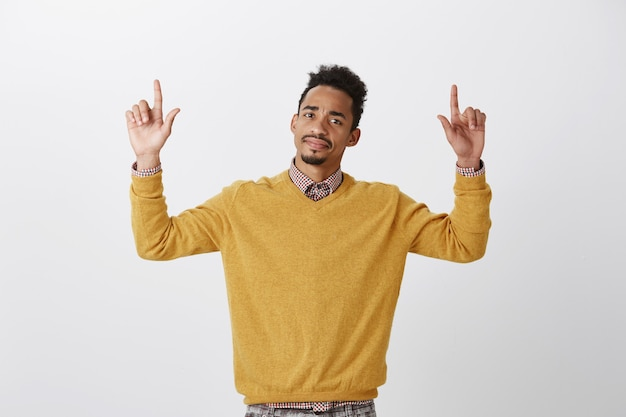 What a disappointment. portrait of displeased doubtful american guy with afro hairstyle raising hands and pointing up with index fingers, expressing disgust and doubt, standing