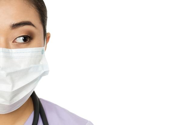 Что мы имеем здесь? обрезанное студийное половину лица крупным планом женщины-врача в хирургической маске, смотрящей на копию пространства сбоку