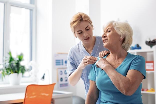 기분이 어떠세요. 마사지를하는 동안 그녀의 환자의 어깨를 만지고 전문 여성 마사지