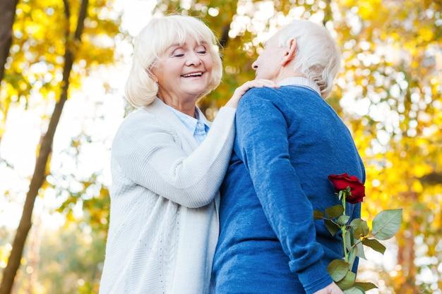 何がありますか?赤を隠している男が後ろに上昇しながらお互いに結合している幸せな年配のカップルのローアングルビュー