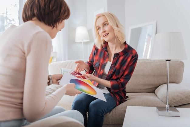 どう思いますか。彼女の友人を見て、彼女の意見を尋ねながら色を指しているうれしそうな素敵なブロンドの女性