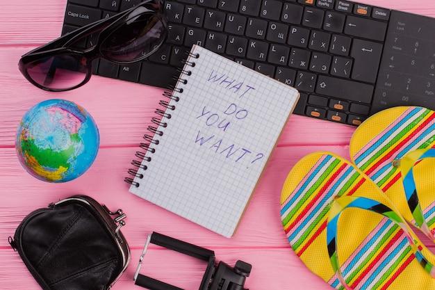 ピンクのテーブルトップの背景に女性の旅行者用アクセサリーメガネウォレットとビーチサンダルを備えたノートブックに何が欲しいですか。グローブと黒のキーボード。
