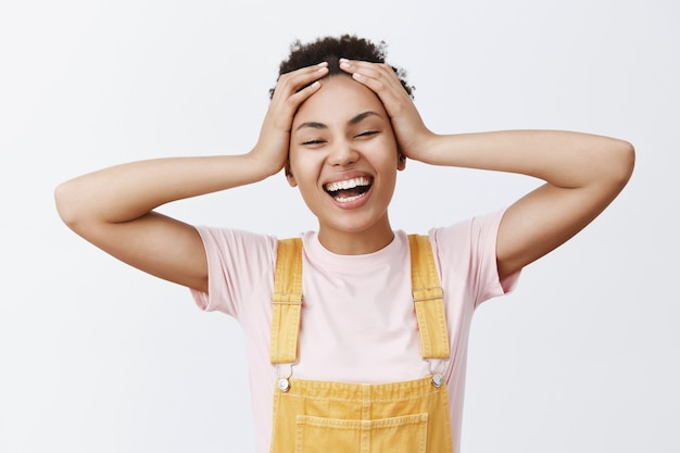 What great time to be alive. portrait of carefree and joyful attractive young african american woman in yellow overalls, touching hair and smiling broadly, feeling happy vacation started