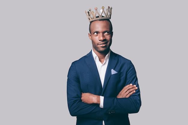 何?王冠と立っている間顔を作るスマートカジュアルジャケットのハンサムな若いアフリカ人