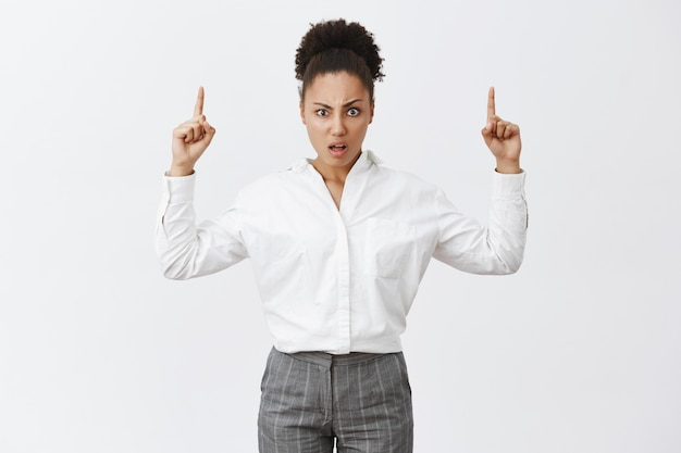 What the heck. portrait of displeased confused african-american female with bun hairstyle in white shirt and pants, staring questioned and disappointed while pointing up with raised hands