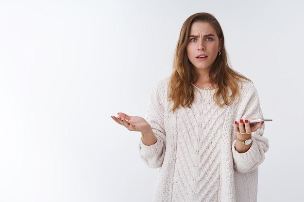 Какого черта. портрет разочарованной, злой, допрошенной, невежественной женщины, спорящей, держащей смартфон, пожимая плечами, распространил тревогу, хмурясь, недоумевающий, открытый рот разговаривает интенсивно, белый фон