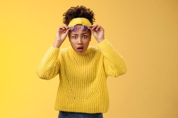 なんてこった。セーターのヘッドバンドの離陸サングラスでショックを受けた唖然とした混乱したアフリカ系アメリカ人のスタイリッシュな現代の女の子は目を広げます驚きの言葉のないあえぎの表情は、フリークアウト、黄色の背景に疑問を呈しました。