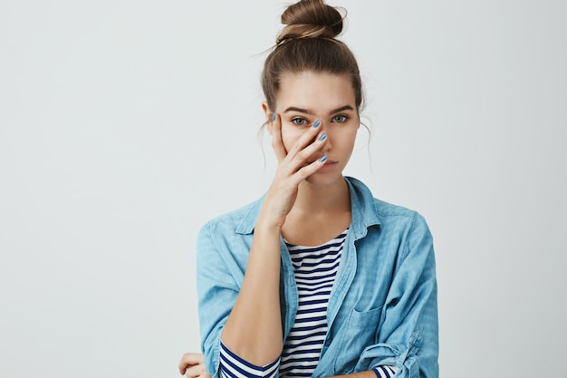 What the hell are you wearing. portrait of girl who feels embarrassed, covering face with palm, looking at something pathetic with unimpressed look, standing