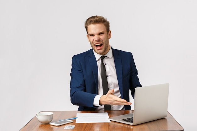 What the hell is that, its really bad. bothered, outraged young boss, businessman in formal suit, sitting office desk, pointing laptop display complaining diagram