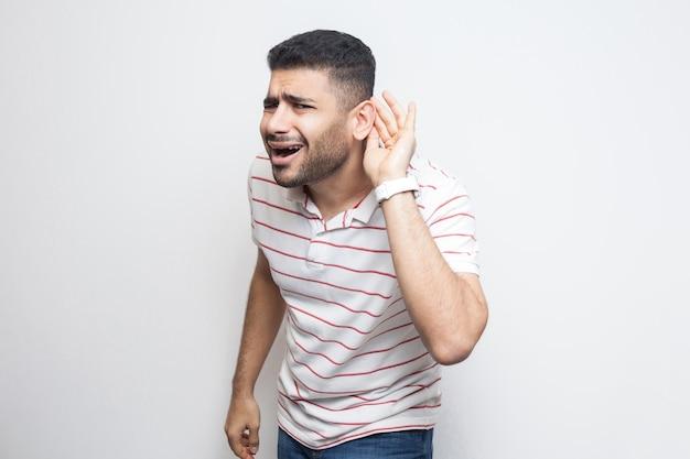 Какие? я вас не слышу. портрет внимательного красивого бородатого молодого человека в полосатой футболке, стоящего с рукой на ухе и желающего что-то услышать. крытая студия выстрел, изолированные на белом фоне.