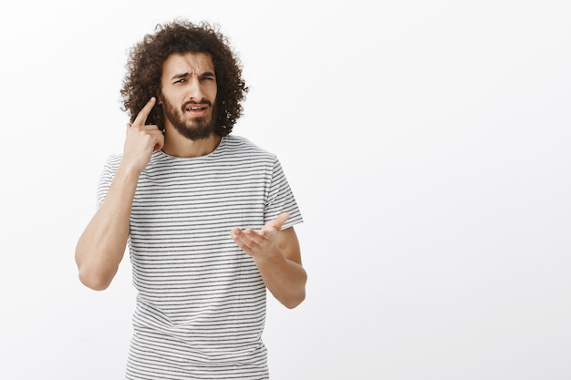 What i cannot hear you, what do you want. portrait of confused bothered handsome eastern guy with afro hairstyle, directing at ear and pointing with palm