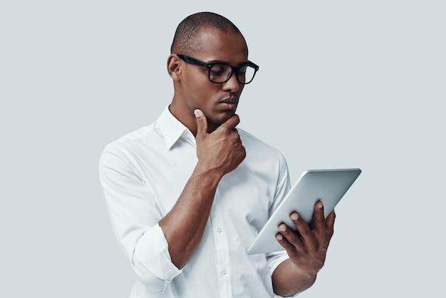 Что, если ... красивый молодой африканец, использующий цифровой планшет и держащий руку за подбородок, стоя на сером фоне