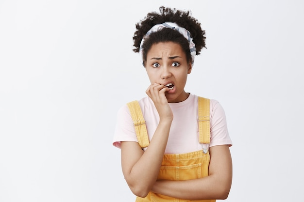 誰かがそれが私だと知ったらどうしますか。トレンディな黄色のオーバーオールとヘッドバンドで肌が黒く、指の爪を噛んで眉をひそめ、心配して動揺して見つめている神経質な有罪のかわいい女性の肖像画