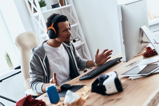 何が起こっている?自宅で時間を過ごしながらコンピューターを使用してカジュアルな服装で欲求不満の若い男