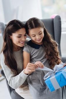 안에 무엇이 있습니다. 어머니의 무릎에 앉아 선물을 열고 안에 무엇이 있는지 궁금해하는 멋진 즐거운 호기심 소녀