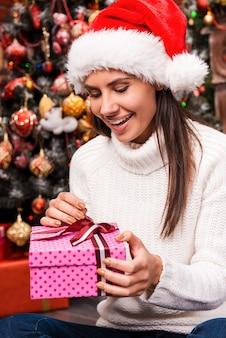 안에 무엇이 있습니까? 산타 모자를 쓰고 선물 상자를 열고 크리스마스 트리 앞에 앉아 웃고 있는 놀란 젊은 여성