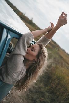 冒険のない人生とは何ですか?車の旅を楽しみながら、バンの窓から身を乗り出し、腕を伸ばしたままの魅力的な若い笑顔の女性