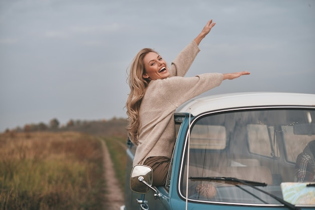 Что такое жизнь без приключений? привлекательная молодая женщина, выглядывающая из окна фургона и улыбаясь, наслаждаясь автомобильным путешествием со своим парнем