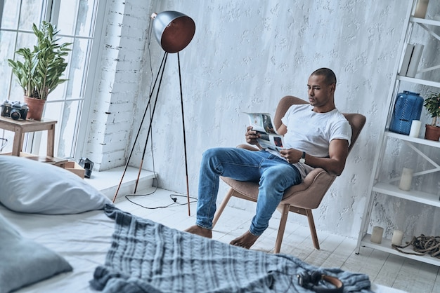 What is new in the world? handsome young african man reading newspaper