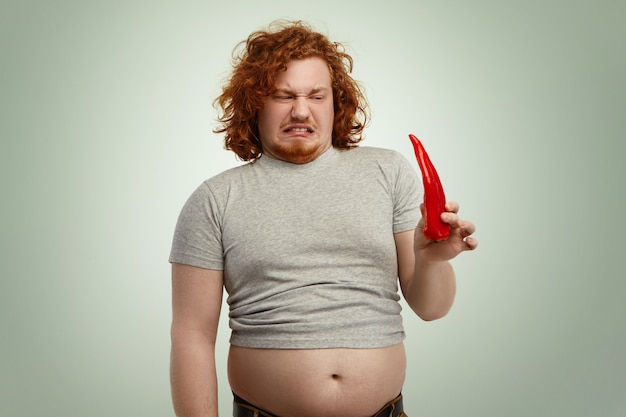 What is that? fastidious young obese overweight man with big stomach making mouths looking in disgust at fresh organic red pepper in his hand while addicted to sugar junk food and carbohydrates