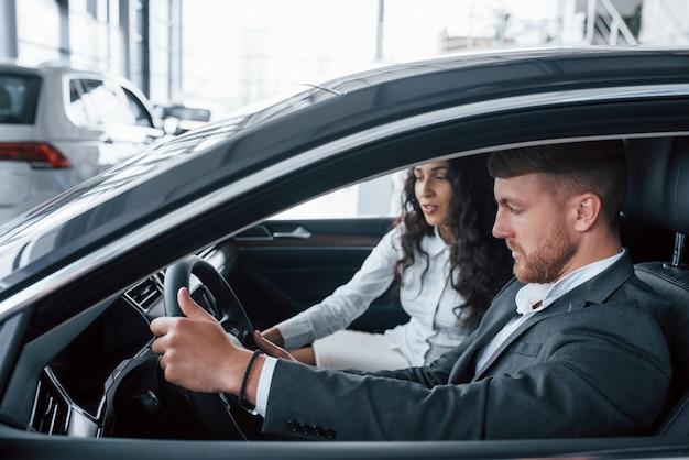 그 기능은 무엇입니까? 자동차 살롱에서 새 차를 시도하는 사랑스러운 성공적인 부부