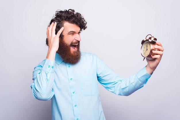 Какой час, бородатый мужчина в непринужденной обстановке боится будильника