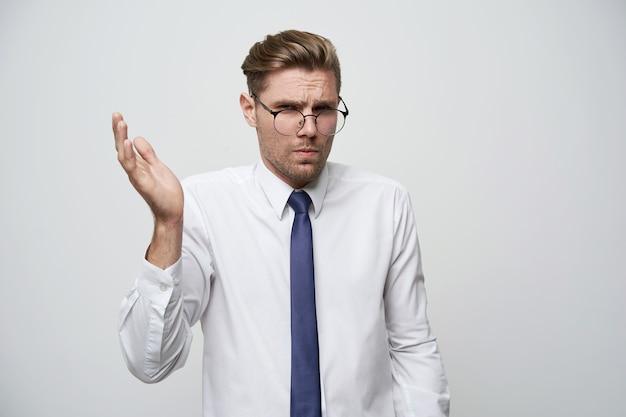 В чем проблема? студийная съемка молодого бизнесмена демонстрирует непонимание