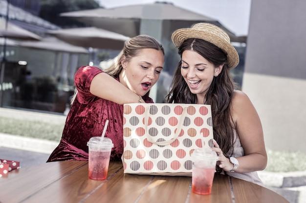 Что здесь. приятные позитивные женщины сидят вместе и заглядывают в сумку
