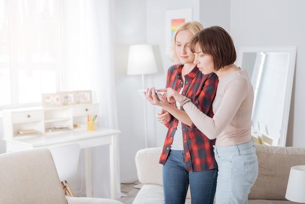 これは何ですか。彼女と一緒に立って、びっくりしながらスマホ画面を見ている嬉しい驚きの若い女性