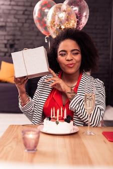 Что это. позитивная радостная женщина трясет подарком на день рождения, думая, что это такое