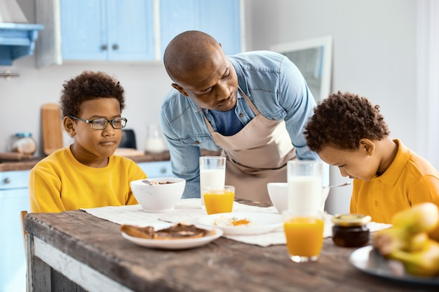 What is wrong. loving young father talking to his upset son, asking him what is wrong, while they having breakfast