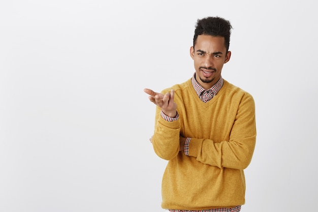 What is your point, dude. portrait of displeased dark-skinned male office worker in yellow pullover holding hands half-crossed, pointing aside with palm, expressing contempt and dislike, arguing