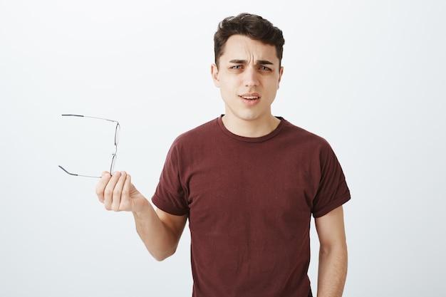 Какова ваша позиция. портрет разочарованного раздраженного красивого взрослого парня в красной футболке Бесплатные Фотографии