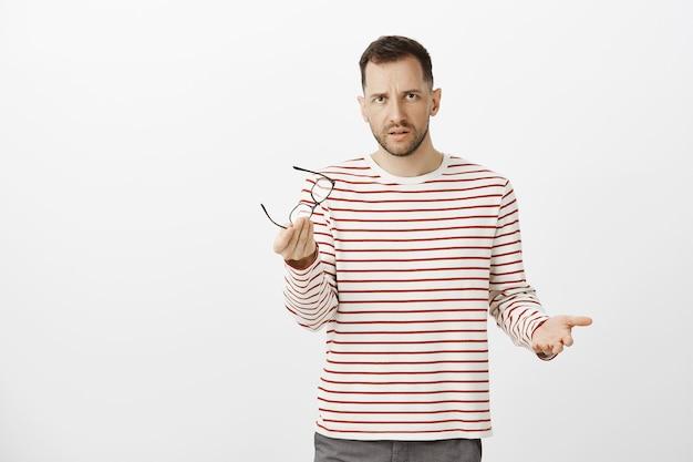 Какова ваша позиция. портрет интенсивного серьезного красивого парня, снимающего очки и жестикулирующего во время обсуждения бизнеса