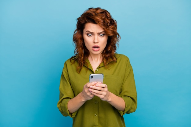 What its unbelievable crazy disappointed blogger woman read incredible social network novelty impressed stare stupor screen wear good look outfit isolated over blue color background
