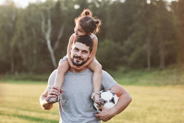今日はなんて素敵な天気でしょう。背景の美しい草や森で彼の娘とお父さんの写真。
