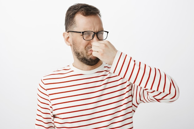 What nasty smell. portrait of displeased disgusted funny guy in glasses, covering nose with fingers and frowning from displeasure, smelling awful reek